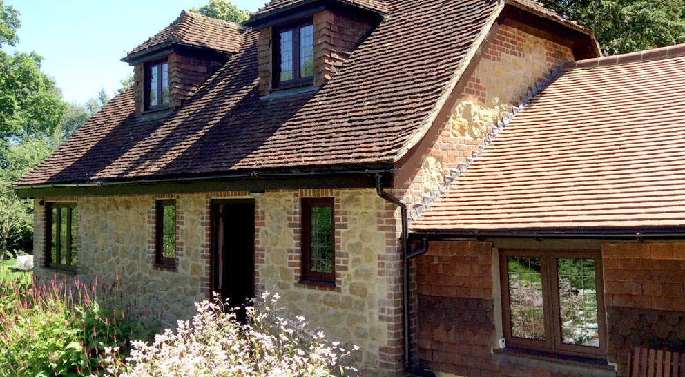 Cottage with dark timber effect uPVC windows